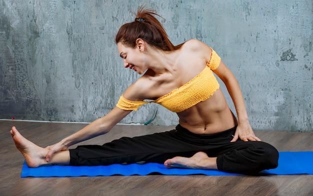 Dziewczyna na macie do jogi robi ćwiczenia rozciągające mięśnie nóg.