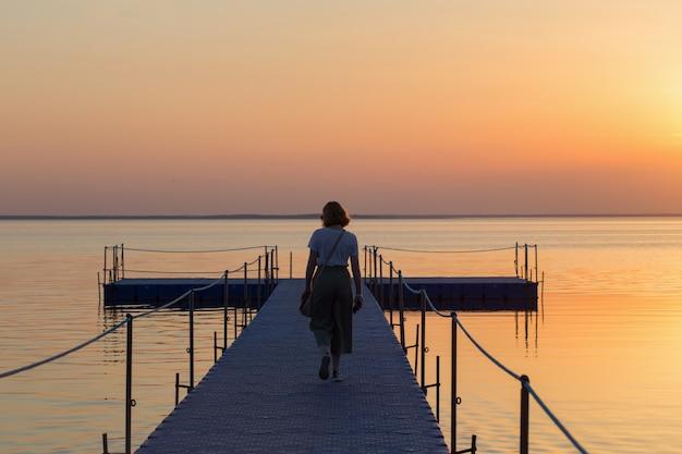 Dziewczyna na molo pontonowym o zachodzie słońca