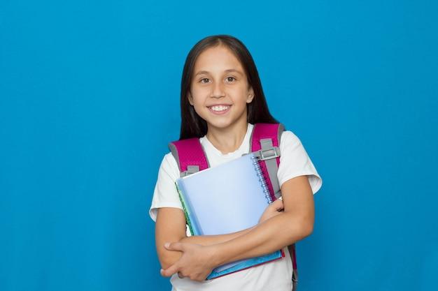 Dziewczyna na niebieskim tle trzymająca koncepcję zeszytów z powrotem do szkoły