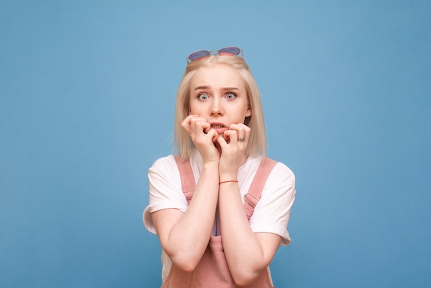 Dziewczyna na niebiesko patrzy zszokowana w kamerę i gryzie palce.