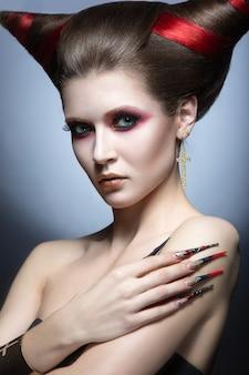 Dziewczyna na obrazie kusiciela-demona z długimi paznokciami i fryzurą w kształcie rogów. zdjęcie zrobione w studio na szarym tle.