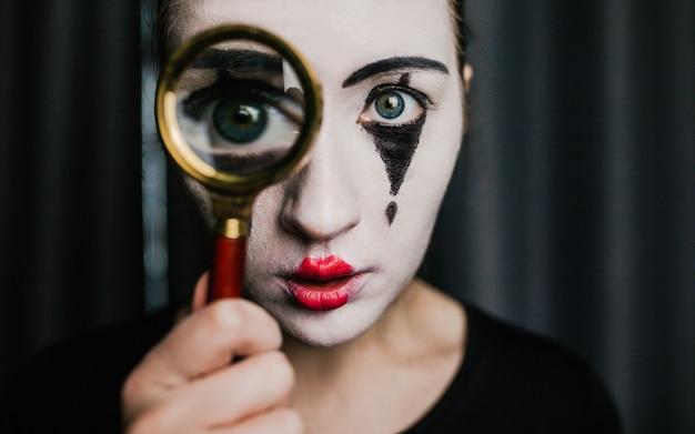 Dziewczyna na obrazie mima trzyma lupę.