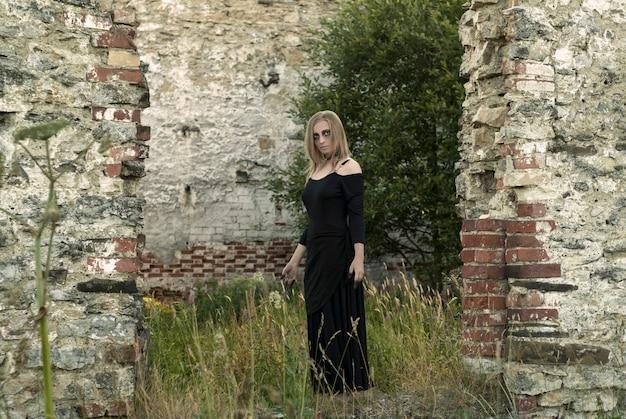 Dziewczyna na obrazie wiedźmy stojącej wśród starożytnych ruin