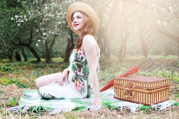 Dziewczyna na pikniku w sadzie jabłkowym z koszem produktów