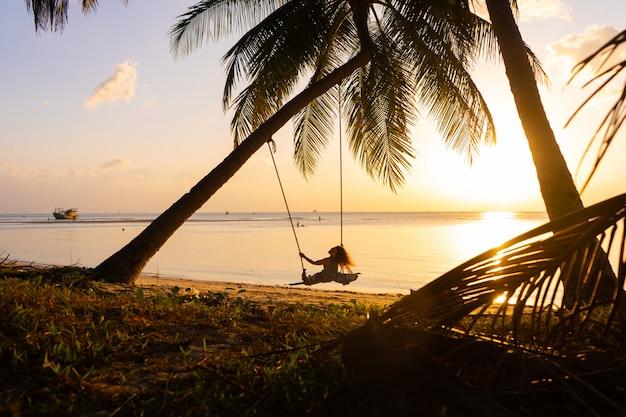 Dziewczyna na plaży jeździ na huśtawce podczas zachodu słońca. zachód słońca w tropikach, ciesząc się przyrodą. huśtawka przywiązana do palmy nad oceanem