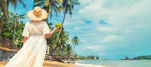 Dziewczyna na plaży pije kokos