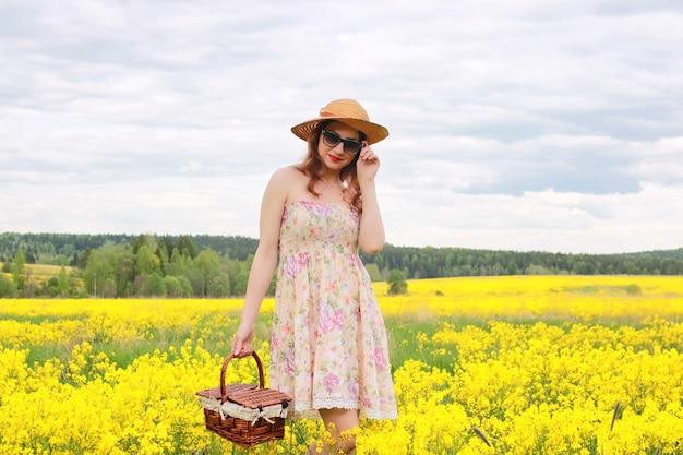 Dziewczyna na polu kwiatów z koszem i kapeluszem