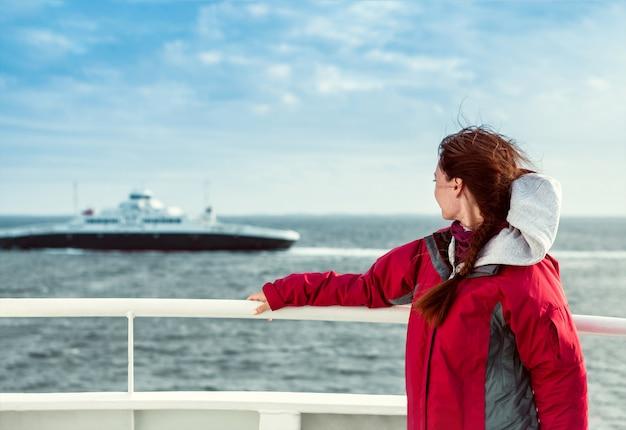 Dziewczyna na promie patrzy w kierunku morza, gdzie pływa liniowiec