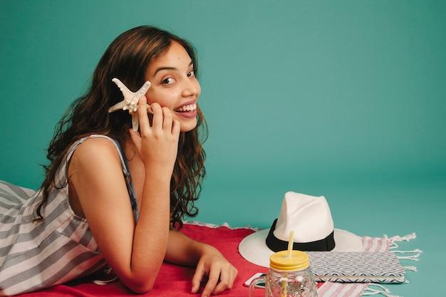 Dziewczyna na ręcznik gospodarstwa rozgwiazdy przy ucha