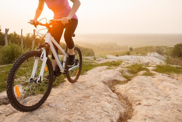 Dziewczyna na rowerze górskim jeździ na szlaku na piękny wschód słońca