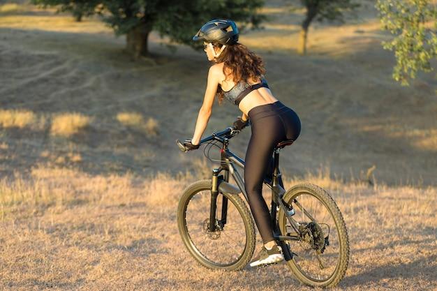 Dziewczyna na rowerze górskim na offroad piękny portret rowerzysty o zachodzie słońca