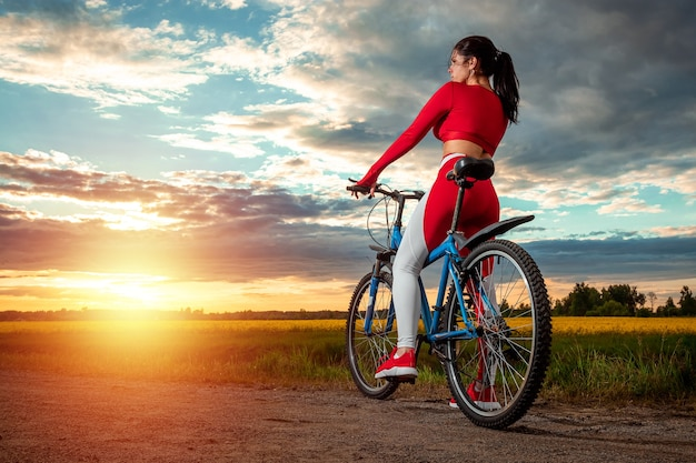 Dziewczyna na rowerze na tle zachodu słońca