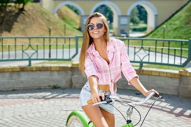 Dziewczyna na rowerze. plenerowy uliczny portret uśmiechnięta młodej kobiety pozycja z rowerem
