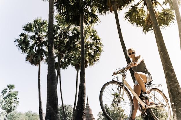 Dziewczyna na rowerze w letni dzień, w tropikalnym miejscu z palmami i promieniami słońca w. zabytkowy styl