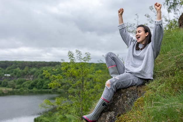 Dziewczyna na spacerze wspięła się na górę w górzystym terenie i cieszy się