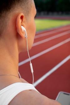 Dziewczyna na stadionie z białą słuchawką w uchu podczas treningu i zbliżenie maratonu