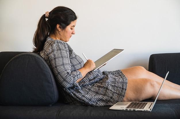 Dziewczyna na sukience odpoczywa na kanapie podczas e-learningu