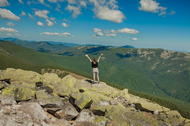 Dziewczyna na szczycie góry podniosła ręce. szeroki letni widok na góry o wschodzie słońca i odległe pasmo górskie objęte. piękno przyrody