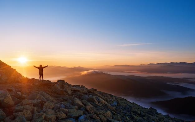 Dziewczyna na szczycie góry z wyciągniętymi ramionami. dramatyczny krajobraz samotnego turysty patrząc na góry we mgle o wschodzie słońca. koncepcja wolności, aktywnego stylu życia i zwycięstwa.