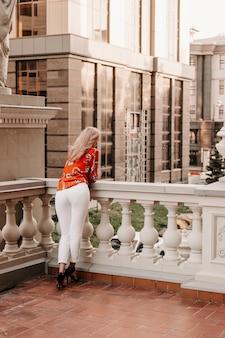 Dziewczyna na tarasie ulicy wygląda, widok z tyłu. blondynka w europie na balkonie