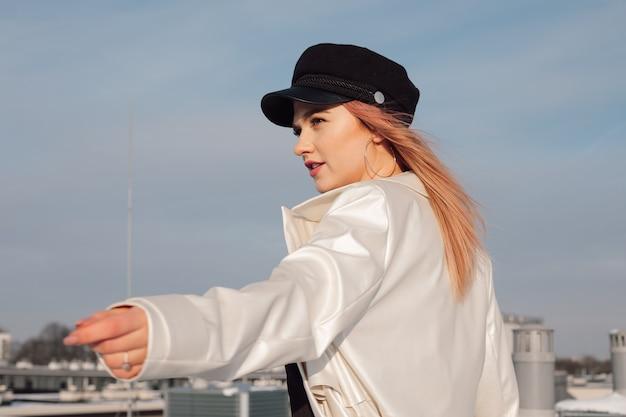 Dziewczyna na tle błękitnego wiosennego nieba w lekkim płaszczu przeciwdeszczowym i czapce na głowie wyciąga rękę w oczekiwaniu.