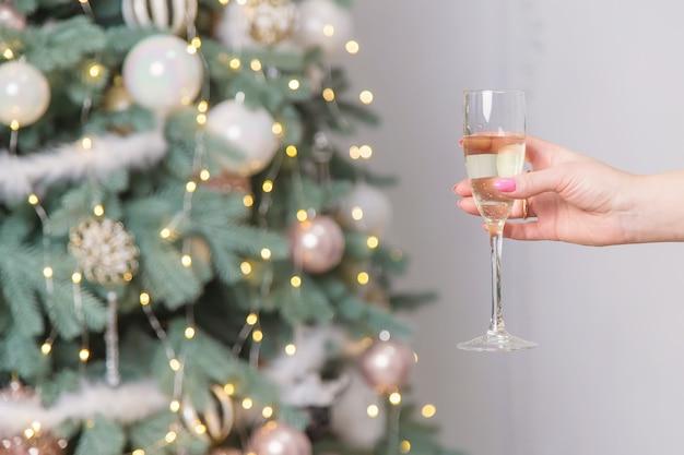 Dziewczyna na tle bożego narodzenia z szampanem. selektywna ostrość. wakacje.