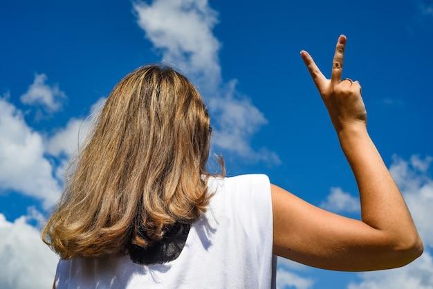 Dziewczyna na tle nieba, odwrócona plecami do aparatu, przedstawia rękę zwycięstwa