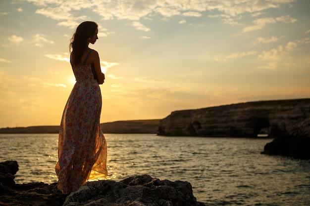 Dziewczyna na tle piękny krajobraz i zachód słońca, sylwetka dziewczyny na klifie, na klifie, piękne niebo i morze