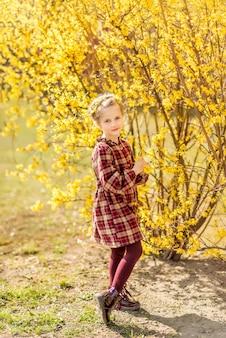Dziewczyna na tle żółtych kwiatów. dziecko w kwitnącym wiosennym ogrodzie
