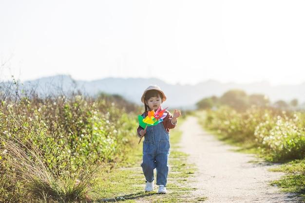 Dziewczyna na trawie w letni dzień trzyma w ręku wiatrak