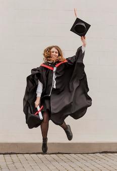 Dziewczyna na ukończeniu szkoły skoki