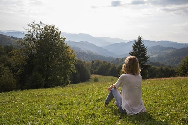 Dziewczyna na wycieczkować wycieczkę cieszy się zmierzchu widok od above. dziewczyna się zrelaksować i odświeżyć na tle gór jest krajobraz wysokich gór, białe chmury. dziewczyna patrzeje pogodnego niebo na górze