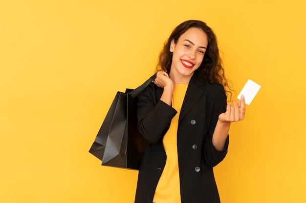 Dziewczyna na zakupach sprzedaży z torbami i kartą kredytową