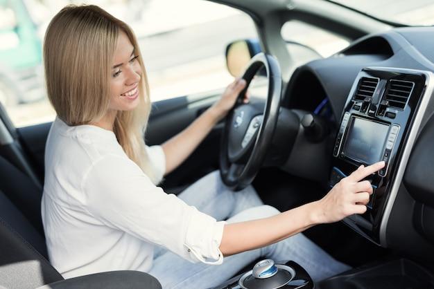 Dziewczyna naciska przyciski na urządzeniach sterujących pojazdu elektrycznego