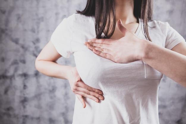 Dziewczyna naciska ręce na ból w klatce piersiowej