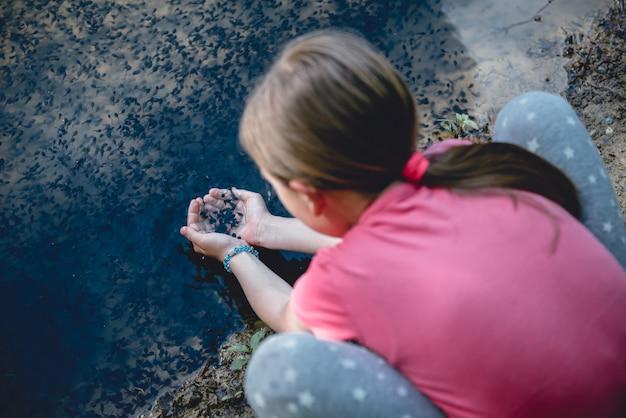 Dziewczyna nad jeziorem łapie kijankę