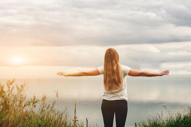 Dziewczyna nad jeziorem widok z tyłu. ręce do góry. zachmurzone niebo, zachód słońca.