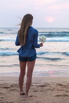 Dziewczyna nad oceanem o zachodzie słońca trzymająca w dłoni kwiat plumerii