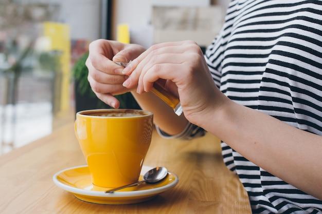 Dziewczyna nalewa cukier z torby do kubka kawy