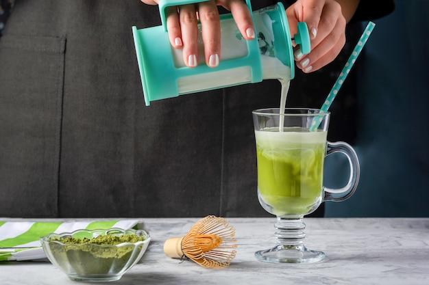 Dziewczyna nalewa mleko do szklanki z zieloną herbatą matcha. proces tworzenia zdrowej latte. przycięte zdjęcie