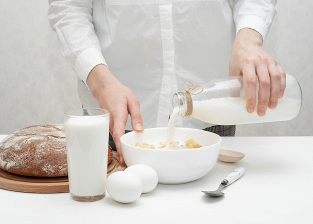 Dziewczyna nalewa mleko w misce ze zbożami