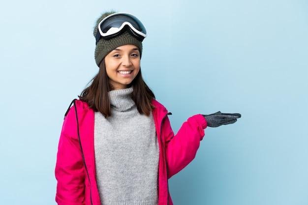 Dziewczyna narciarz rasy mieszanej z okularami snowboardowymi na izolowanych niebieską ścianą trzymającą wyimaginowane copyspace na dłoni, aby wstawić reklamę