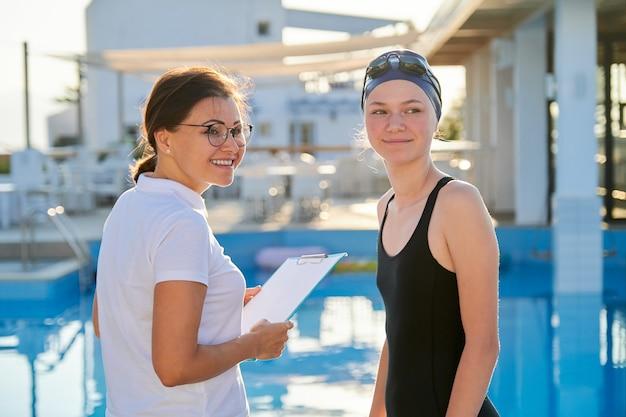 Dziewczyna Nastolatek Pływaczka W Sportowej Czapce Strój Kąpielowy Z Trenerem Kobiety W Pobliżu Odkrytego Basenu, Aktywny Zdrowy Styl życia Młodzieży Premium Zdjęcia