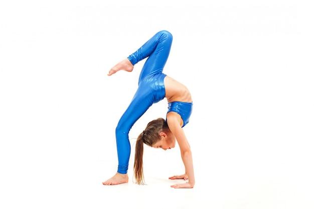 Dziewczyna nastolatek robi ćwiczenia gimnastyczne na białym tle