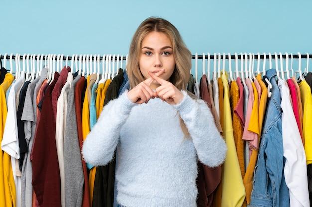 Dziewczyna nastolatka kupuje jakieś ubrania na białym tle na niebiesko przedstawiający znak gestu ciszy