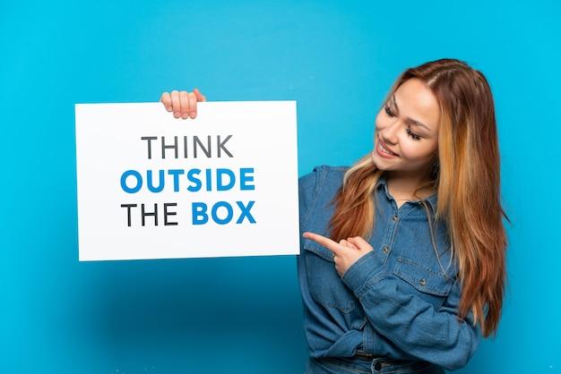 Dziewczyna nastolatka na pojedyncze niebieskie tło trzyma tabliczkę z tekstem think outside the box i wskazuje go