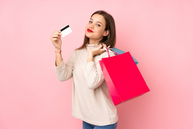 Dziewczyna nastolatka na różowym gospodarstwa torby na zakupy i karty kredytowej