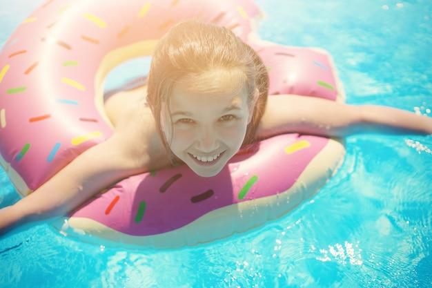 Dziewczyna nastolatka w stroju kąpielowym pływa z nadmuchiwanym pierścieniem w basenie z niebieską wodą.