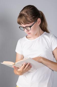 Dziewczyna nastolatka z książką i w okularach na szarym tle