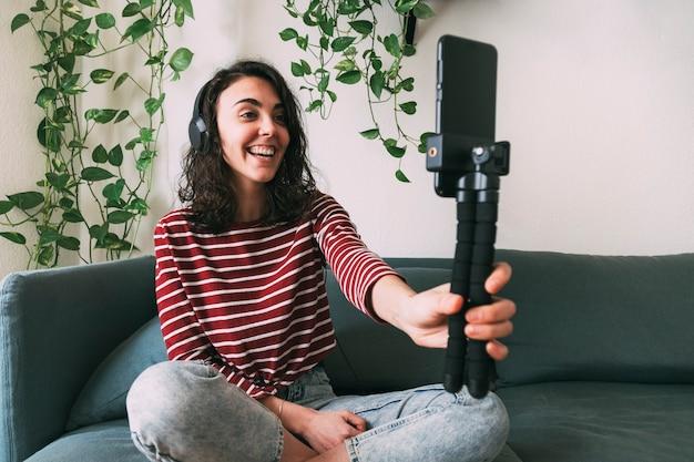Dziewczyna nawiązuje połączenie wideo z telefonu ze słuchawkami w domu. koncepcja technologii